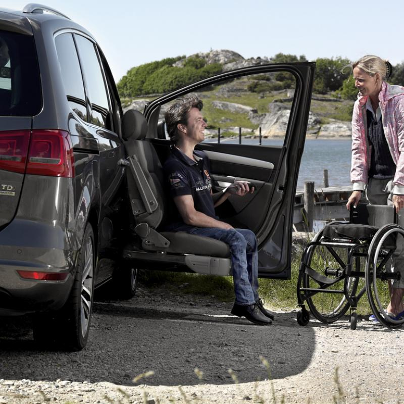 Carer brings a wheelchair to a user sitting in a seat lift of a car.